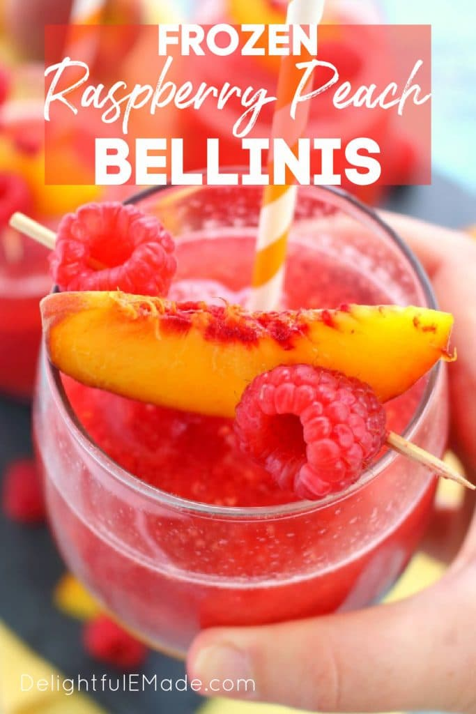 Hand holding a glass of frozen peach bellini topped with fresh peach slices and raspberries.