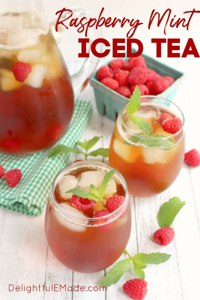 Glasses and pitcher of raspberry mint iced tea, with fresh raspberries and mint sprigs.