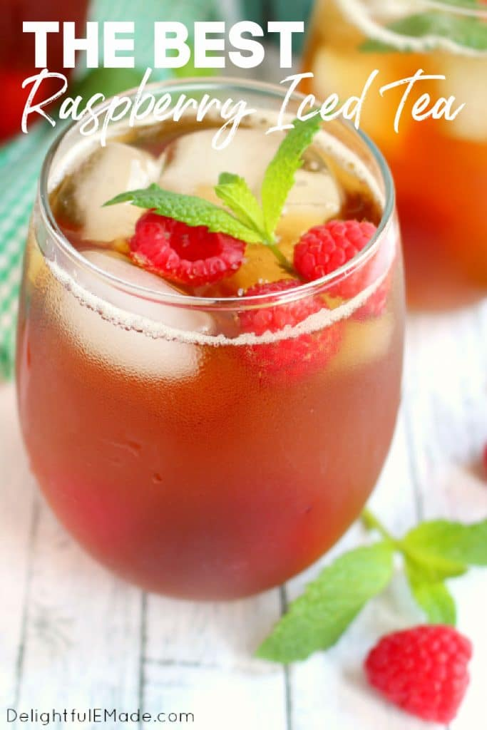 Glass of raspberry mint iced tea topped with fresh raspberries and mint sprig.