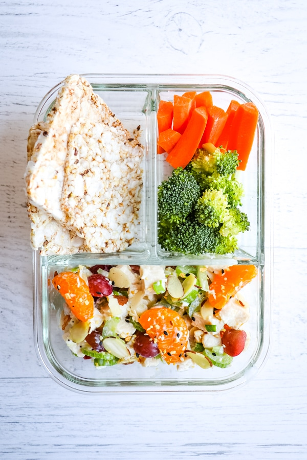Greek yogurt chicken salad in meal prep container with veggies and rice cakes.