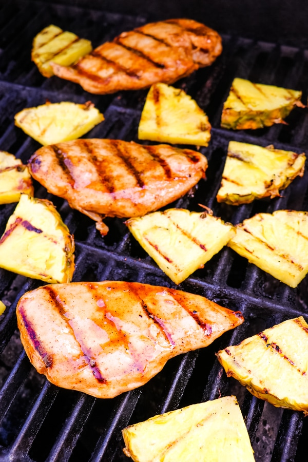 Pineapple grilled chicken with pineapple slices on grill.