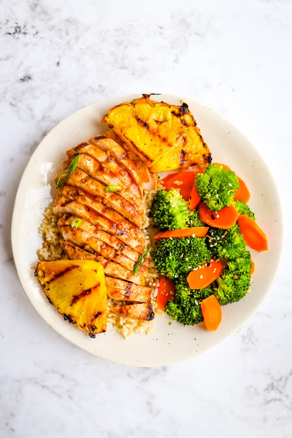 Pineapple grilled chicken, sliced and served with rice and steamed vegetables.