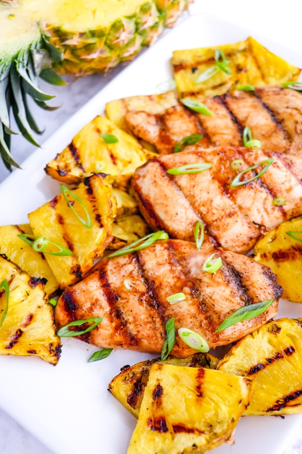 Pineapple grilled chicken on platter, garnished with sliced green onions.
