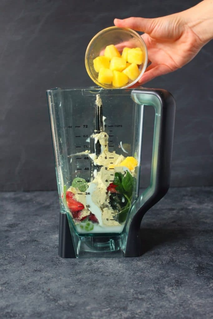 Layering smoothie ingredients into a blender