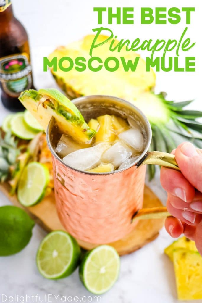 Pineapple Moscow Mule recipe in copper mug, garnished with lime and pineapple slices.