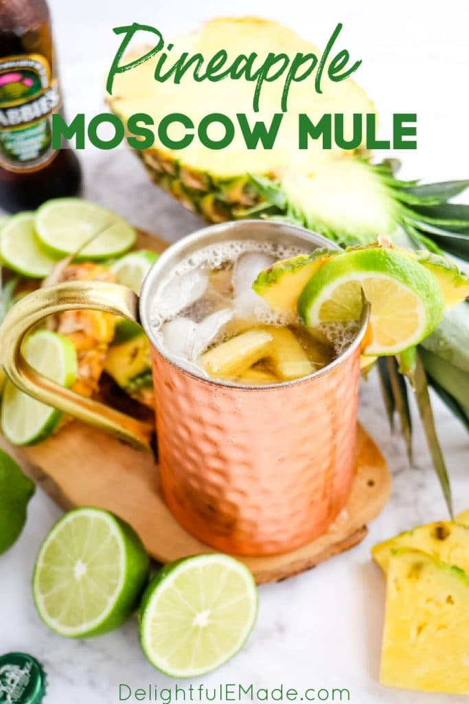 Pineapple Moscow Mule in copper mug, garnished with limes and pineapple wedge.