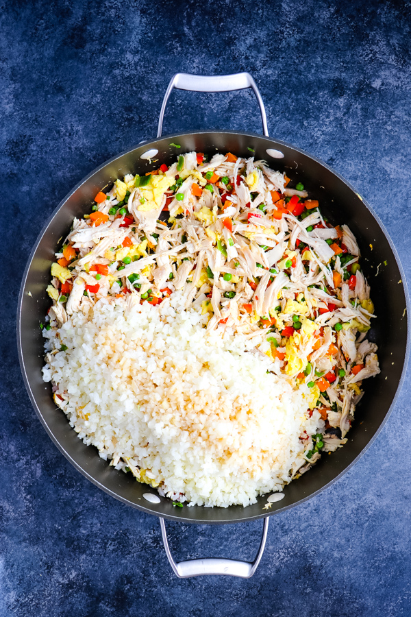 ingredients for chicken fried rice with cauliflower rice and soy sauce in skillet.