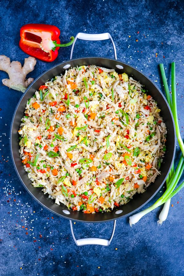 cauliflower chicken fried rice in skillet, garnished with green onions.